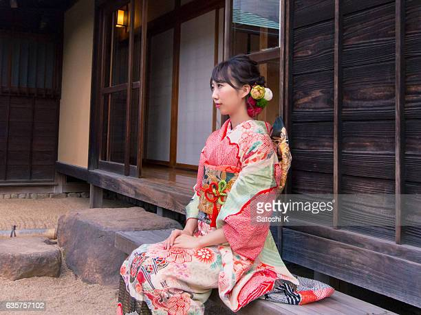 Young Furisode woman sitting on bench at stone garden