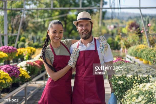 giovani giardinieri al centro giardino - bicolore colore foto e immagini stock