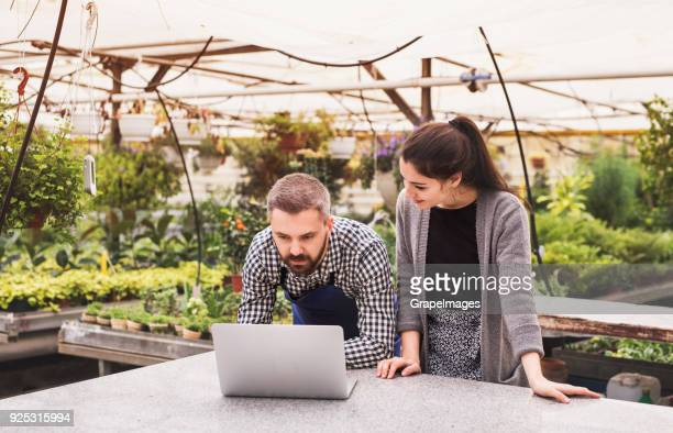Young gardeners with laptop in a large greenhouse with pots of seedlings.