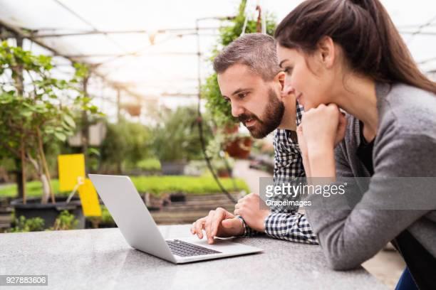 jovens jardineiros com laptop em uma grande estufa com potes de mudas. - environment - fotografias e filmes do acervo