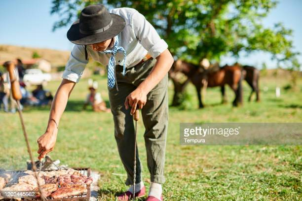 young gaucho grilling meat in the traditional argentinian way. - argentina america del sud foto e immagini stock