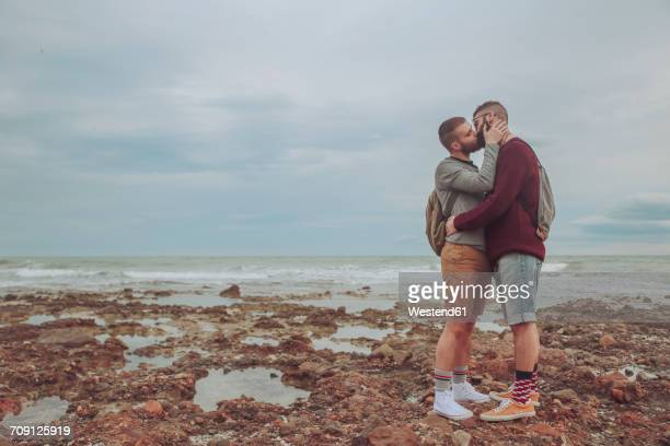 Young gay couple kissing on the beach