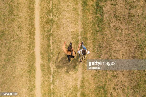 young gay couple with backpacks walking side by side, top view - fianco a fianco foto e immagini stock