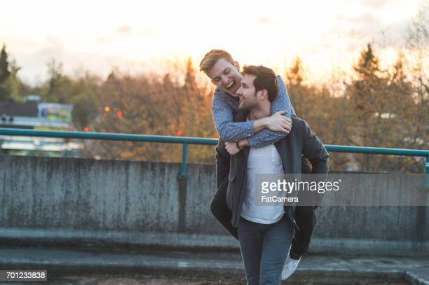 young gay male couple enjoy a beautiful sunset outside together - bisexuality stock photos and pictures