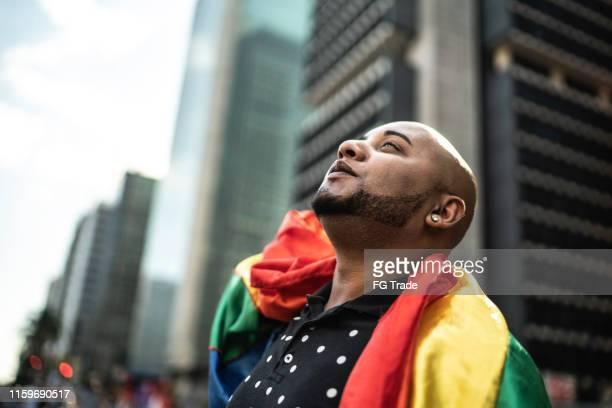 homem gay novo que prende a bandeira do arco-íris durante a parada do orgulho - desfiles e procissões - fotografias e filmes do acervo
