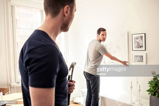 Young gay man looking over shoulder at partner while hanging frame on wall in home