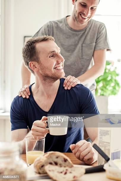 Young gay man massaging partner having breakfast at table