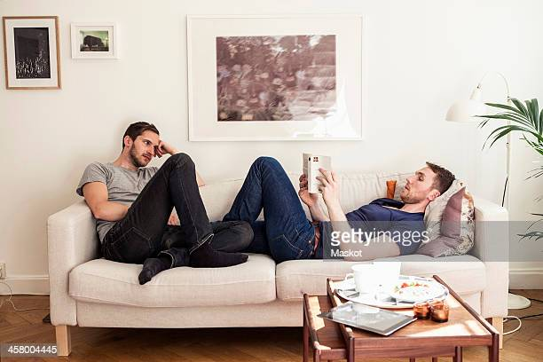 Young gay man reading book while partner looking at him on sofa