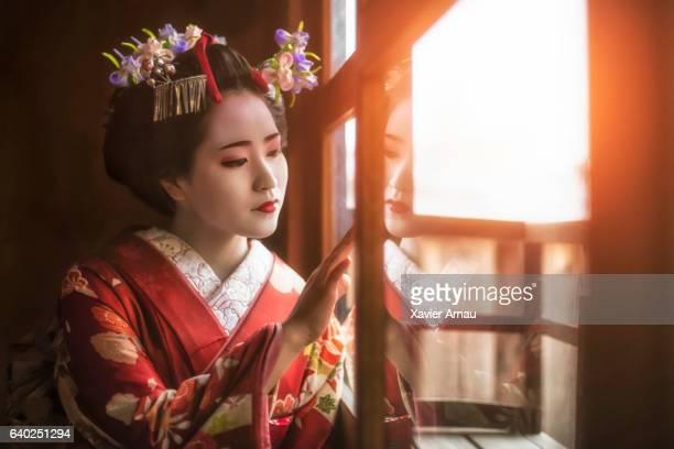Young geisha girl looking through window
