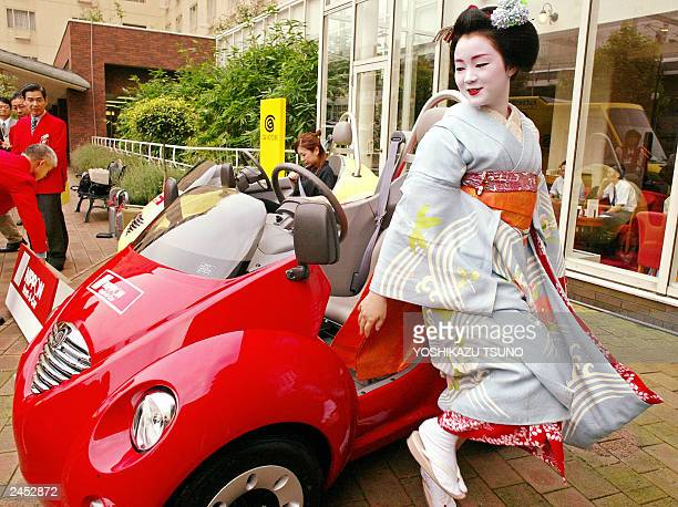Young geisha girl or Maiko girl Suzuko gets out of a small electric vehicle Qi produced by Japan's toy giant Takara as Japan's rentacar operator...