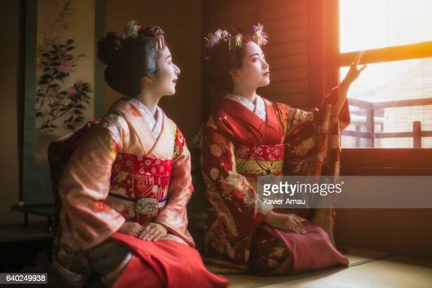 Young geisha girls looking through window
