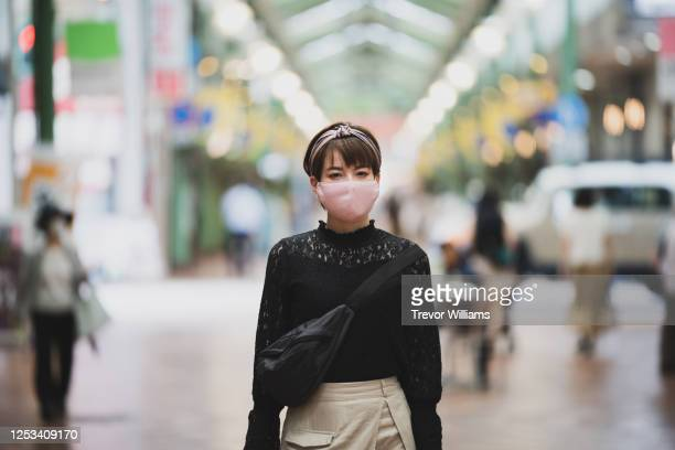 young gen z aged woman shopping with protective face masks on - japan economy stock pictures, royalty-free photos & images