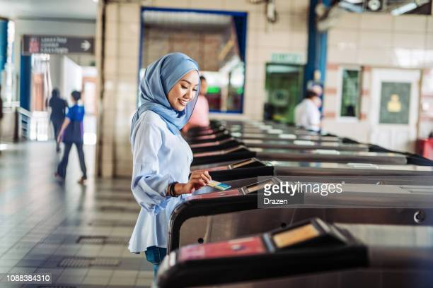 young gen z woman with hijab using public transport - public transport stock pictures, royalty-free photos & images