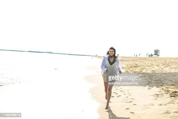 junge generation z frau genießt seal beach in kalifornien läuft am rande des ozeans in der nähe der wellen und wasser - dicke frauen am strand stock-fotos und bilder