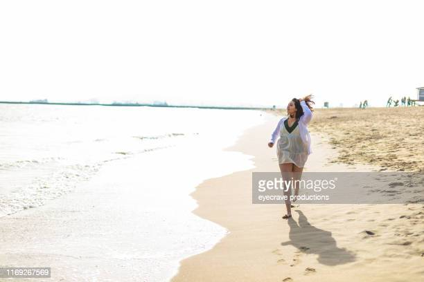young Generation Z woman enjoying Seal Beach in California running on the edge of the ocean near the waves and water