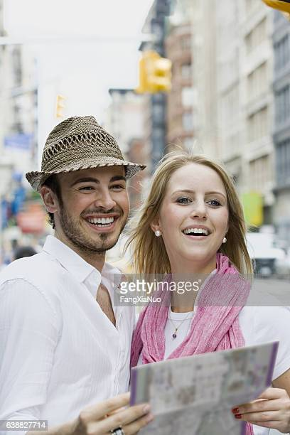 Young German couple holding map in downtown city