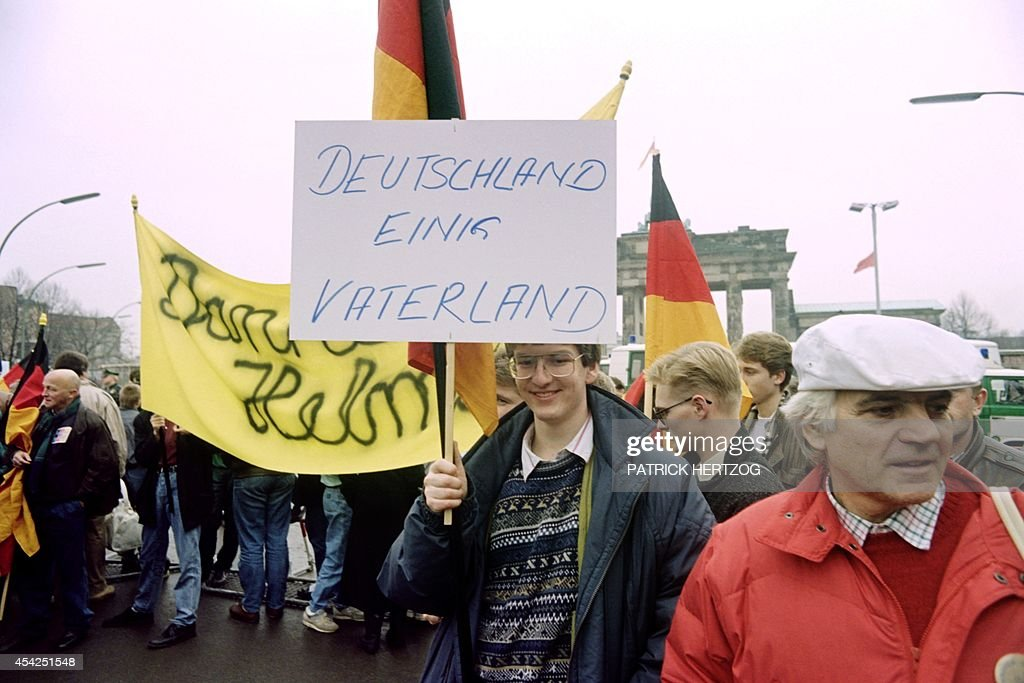 A young German holds a banner reading 'Deutschland einig Vaterland'.....'Germany - One Nation' or 'Germany united fatherland', during a demonstration in front of Brandenburg Gate, east Berlin, on December 22, 1989. On November 09, Gunter Schabowski, the East Berlin Communist party boss, declared that starting from midnight, East Germans would be free to leave the country, without permission, at any point along the border, including the crossing-points through the Wall in Berlin. The Berlin concrete wall was built by the East German government in August 1961 to seal off East Berlin from the part of the city occupied by the three main Western powers to prevent mass illegal immigration to the West. According to the 'August 13 Association' which specialises in the history of the Berlin Wall, at least 938 people - 255 in Berlin alone - died, shot by East German border guards, attempting to flee to West Berlin or West Germany.