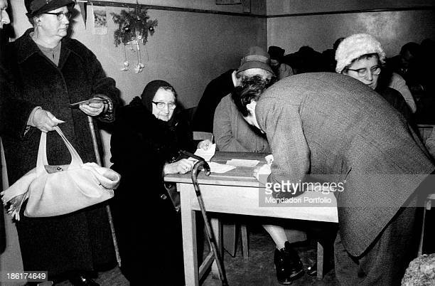Young German man helping Anna Feininger in the filling of the form for her pass The old woman stood in a queue for hours to see after two and a half...