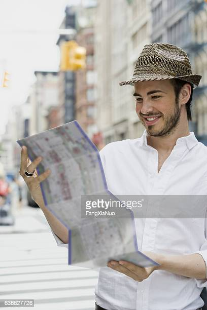 Young German man reading map in downtown city