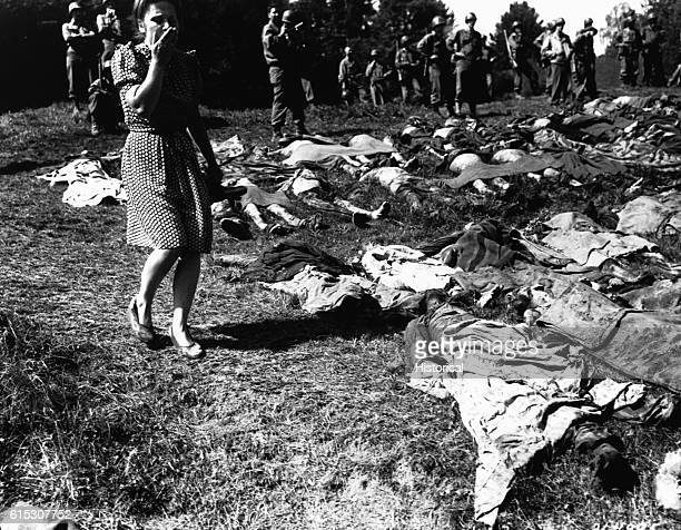 A young German woman is overcome as she walks past the exhumed bodies of some 800 slave workers murdered by SS guards near Namering Germany and laid...