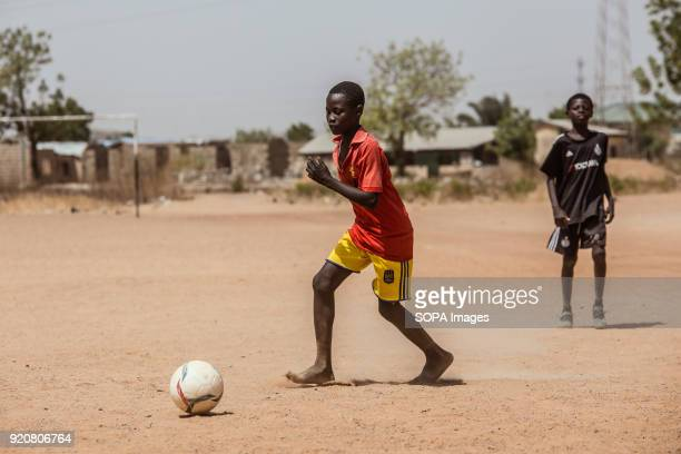 A young Ghanaian boy plays football with bare feet at TimTooni Football Club just outside Tamale in Northern Ghana Along with football coaches from...