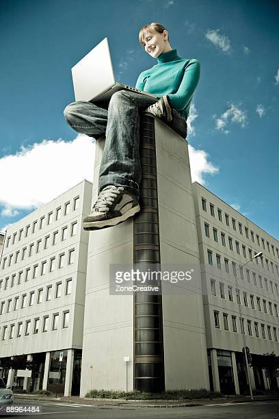 Young giant girl using laptop seated on building