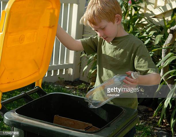 Young ginger boy recycling his bottle