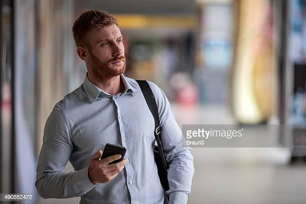 jengibre joven empresario mediante teléfono móvil al aire libre y mirando lejos. - ginger lee fotografías e imágenes de stock