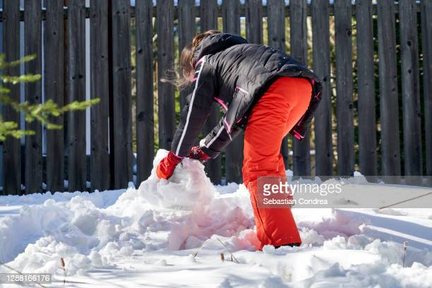young girl 10 years  building a snow fortress, snow winter playing building. - 10 11 years stock pictures, royalty-free photos & images