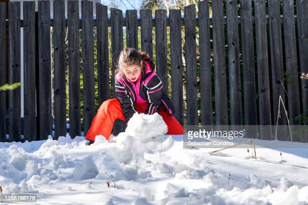 young girl 10 years builds fort in deep snow bank. - 10 11 years stock pictures, royalty-free photos & images