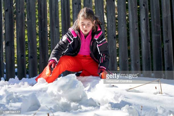 young girl 10 years trying to build a fortress out of snow. - 10 11 years stock pictures, royalty-free photos & images