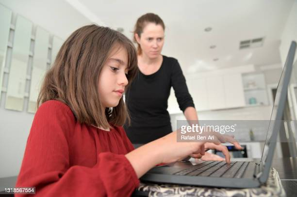 young girl a laptop computer at home while mother supervising here - rafael ben ari stock pictures, royalty-free photos & images