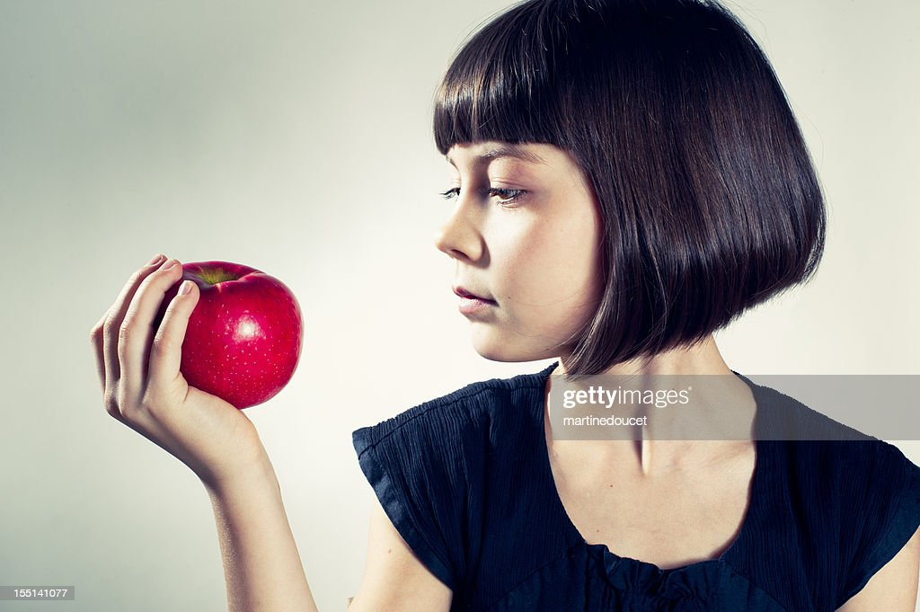 Young girl about to eat a red apple. : Stock Photo