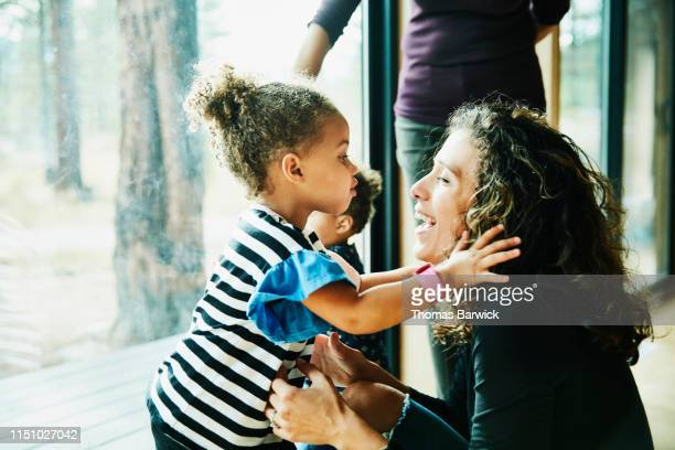 Young girl about to kiss laughing mother