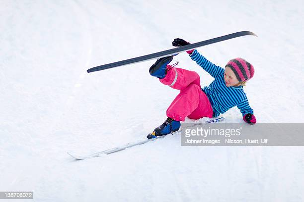 young girl adjusting skis - chute ski photos et images de collection