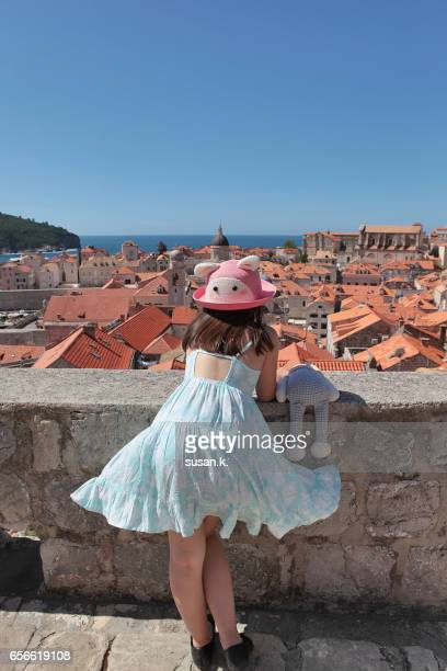 Young girl admiring beautiful medieval town with her stuffed bunny.