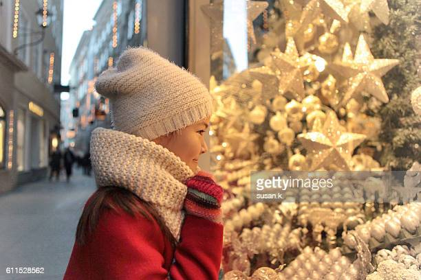 Young girl admiring shiny christmas ornaments at the shop window.