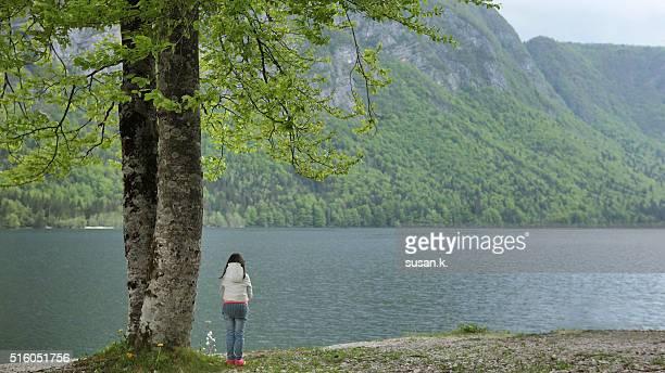 young girl admiring the tranquil lake scene. - kranj fotografías e imágenes de stock