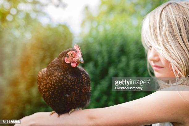 Young Girl Affectionately Holding a Chicken