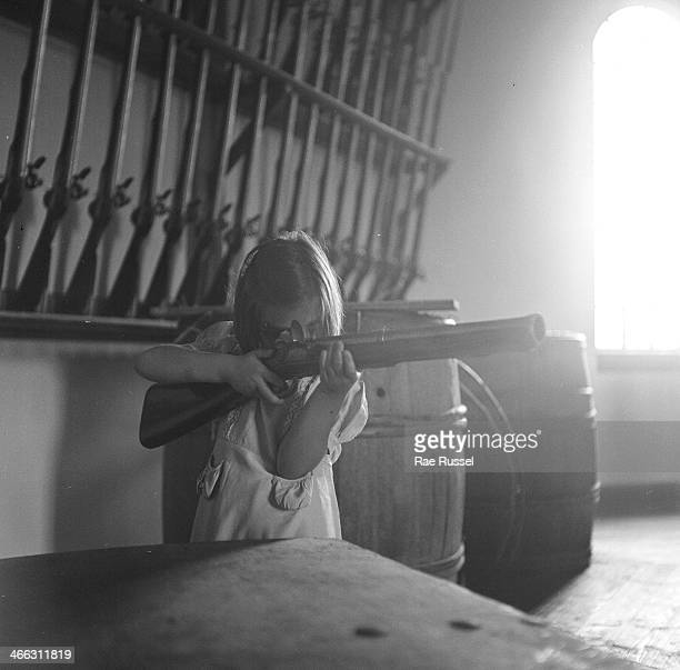 A young girl aims an antique blunderbuss a row of antique rifles is visible on the wall behind her 1949