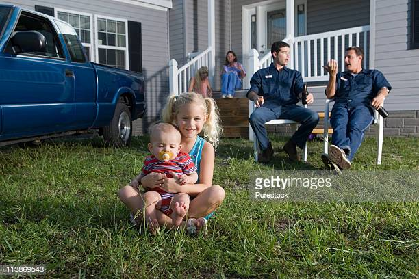 Young girl and a baby sitting on the front lawn of a trailer home, family in background