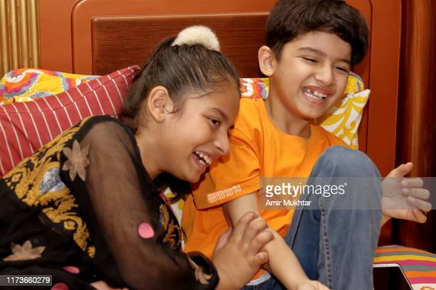 a young girl and a boy enjoying, laughing and having fun on bed in bedroom - punjab pakistan stock pictures, royalty-free photos & images