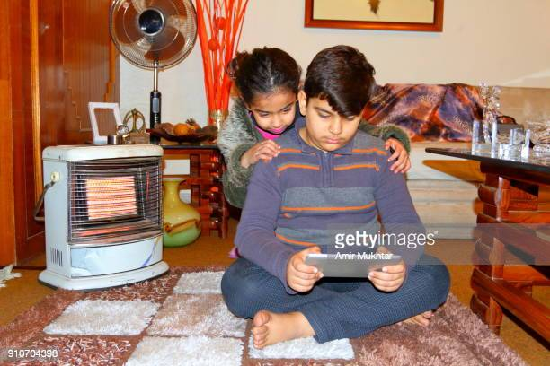 Young Girl And A Boy Enjoying While Using Tablet
