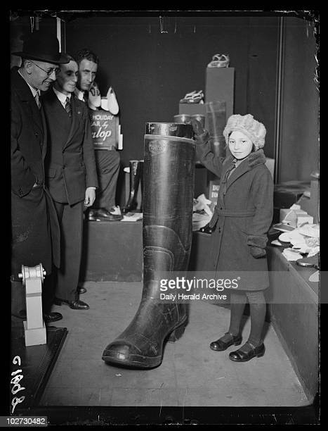 Young girl and a giant Wellington boot 1933 A photograph of a young girl standing next to a giant Wellington boot at Dunlop's shop in Charing Cross...