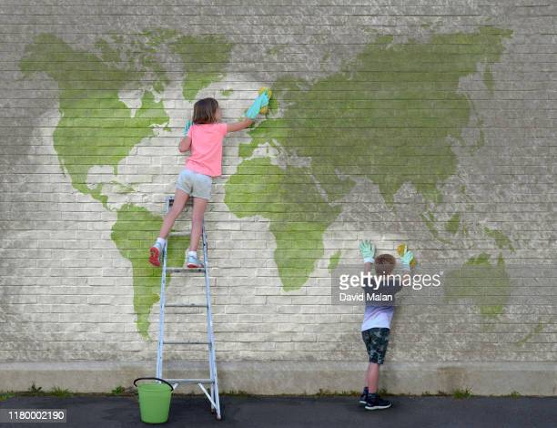 a young girl and a young boy cleaning dirt off a world map mural. - environmental damage stock pictures, royalty-free photos & images