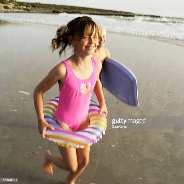 Young girl (7-8) and a young boy (8-9) running at the beach holding beach gear