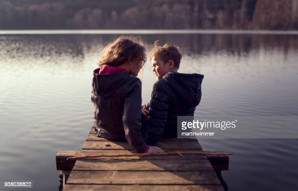 junge Mädchen und jungen an einem hölzernen Pier an einem See in Österreich