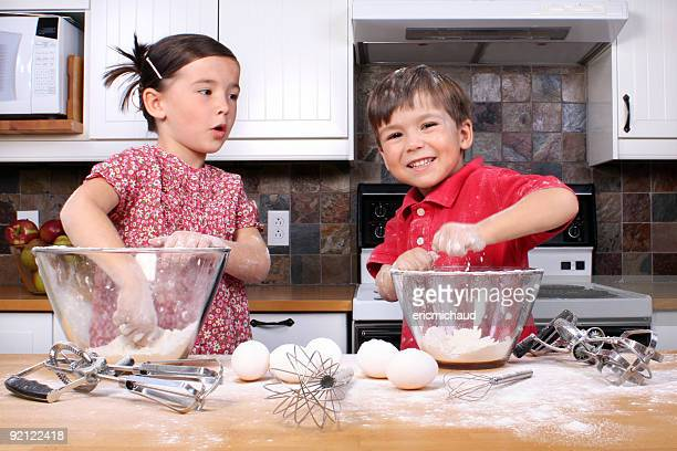 Young girl and boy cocinar juntos