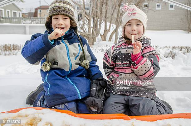 Young girl and boy eating maple syrup taffy outside