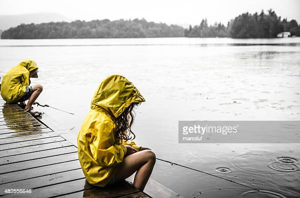 Young girl and boy fishing under rain